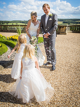 flower girls throw confetti on terrace at harewood house near Leeds www.oliviabrabbs.co.uk