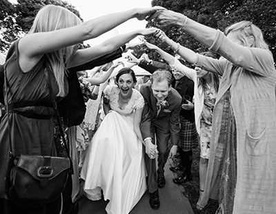 documentary wedding photography of bride and groom leaving marquee